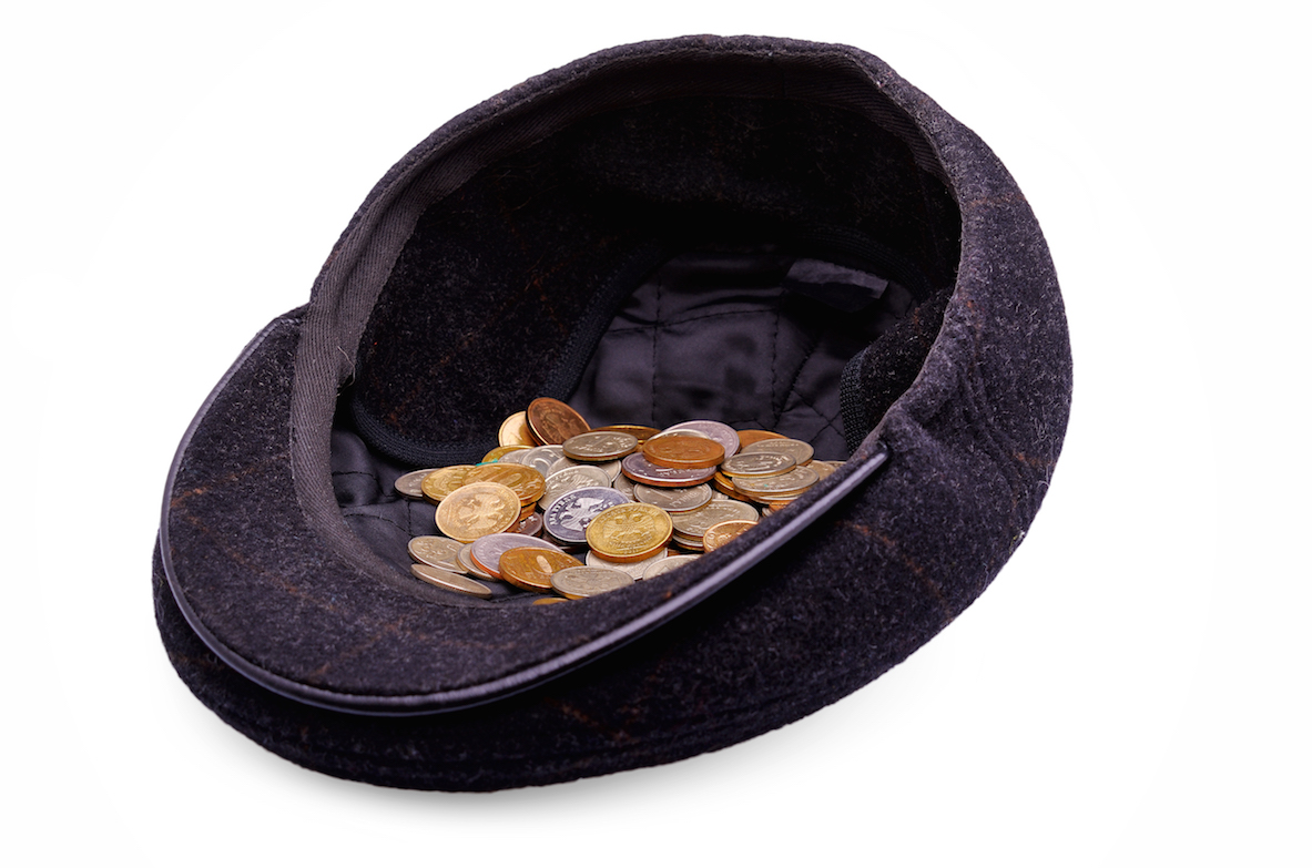 Coins in a cap on a white background