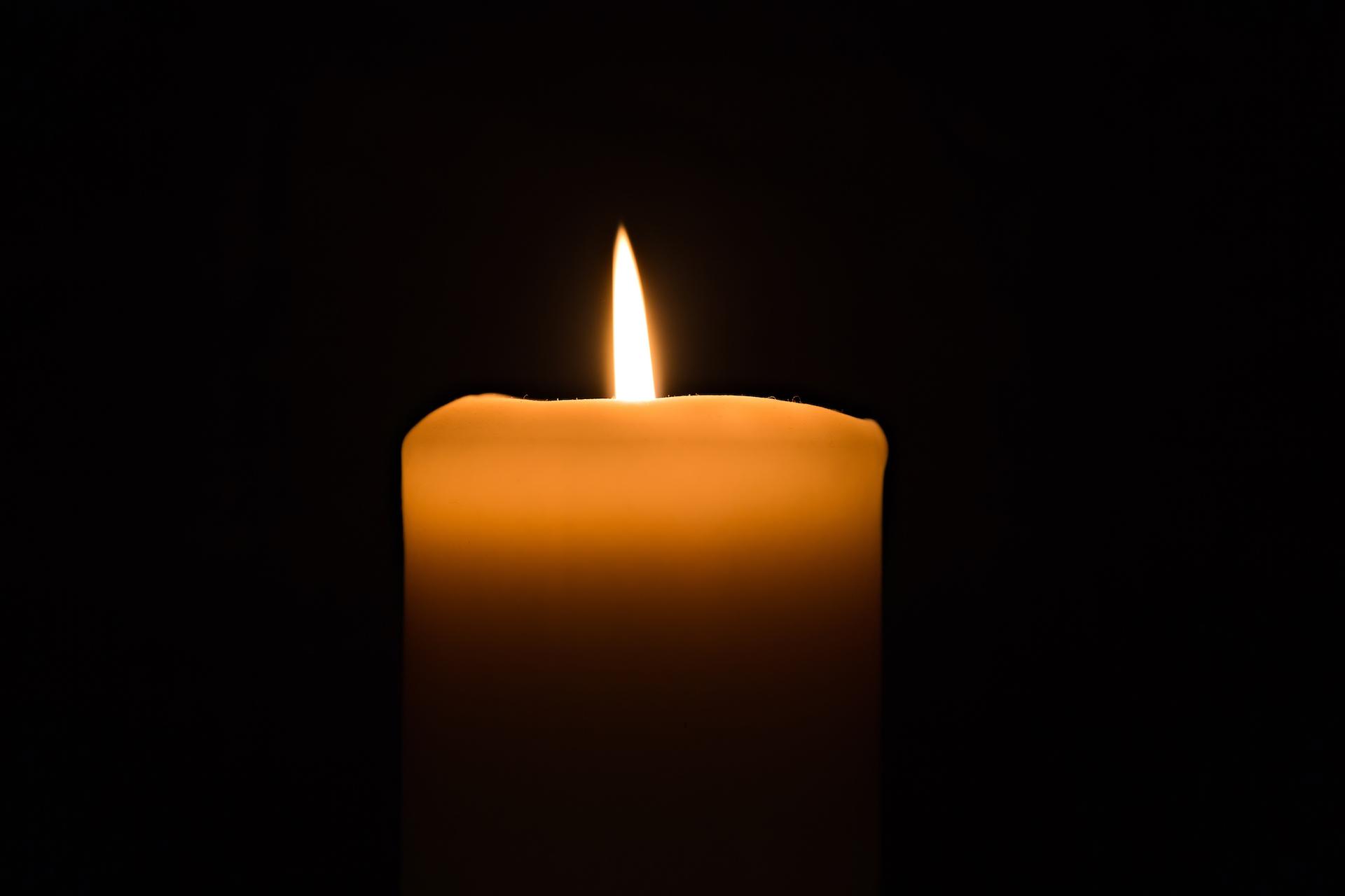 Single candle burning burning brightly in the black background.